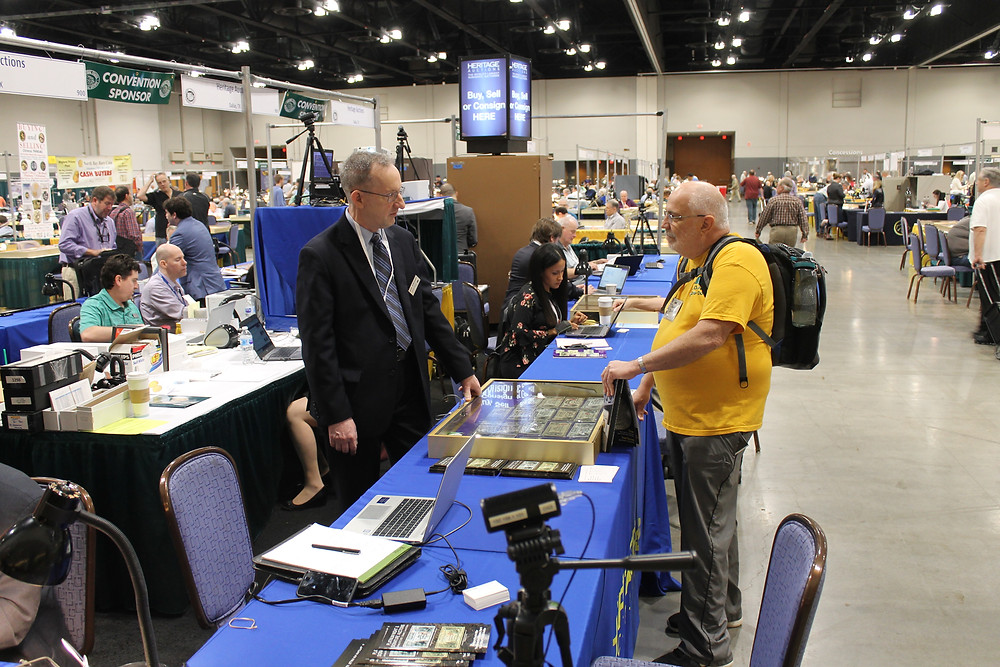 Public attendee standing at the Heritage Auctions table talking to a Heritage representative.