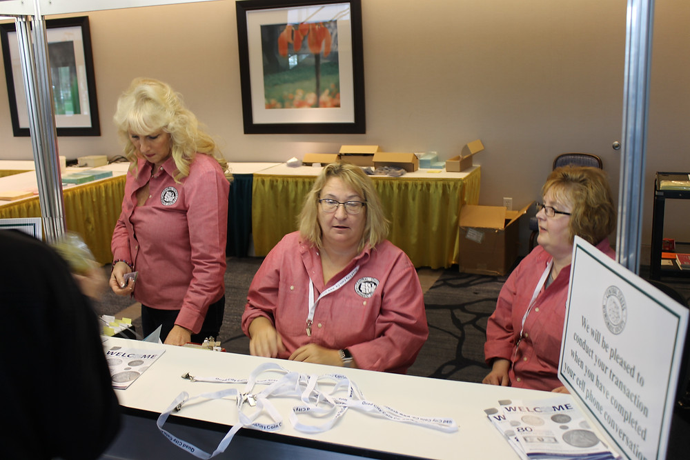 Three women in pink Central States shirts register attendees for the 80th Anniversary Convention