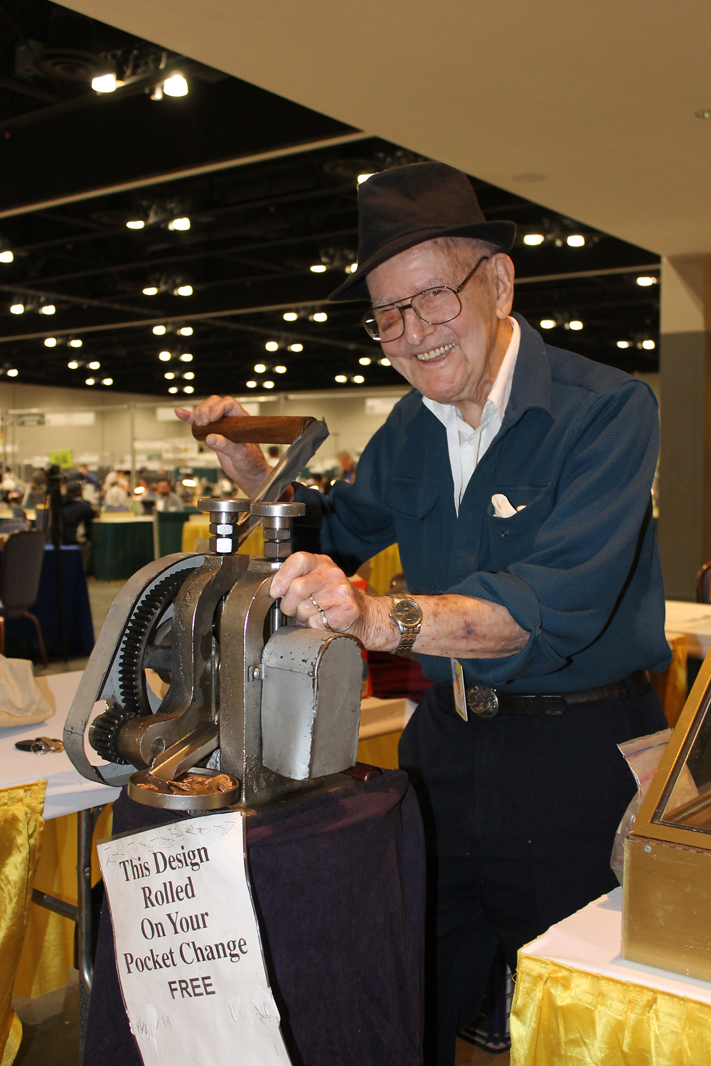 Ray Dillard wearing a fedora, smiling while standing next to a penny rolling machine. Sign on the machine reads this design rolled on your pocket change free.