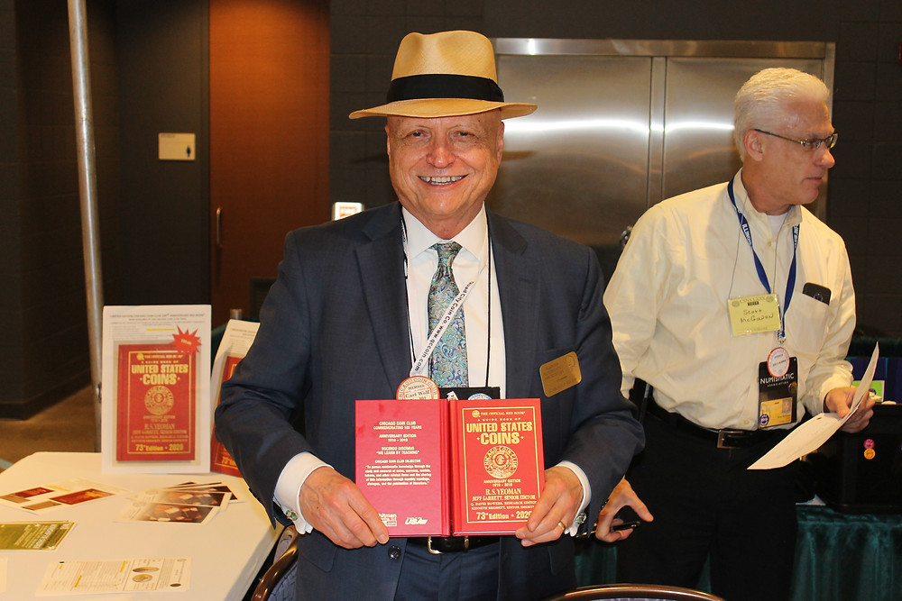 Man in a suit and yellow fedora smiling while holding a Red Book of US Coins