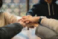 Image of five hands overlaying denoting teamwork.