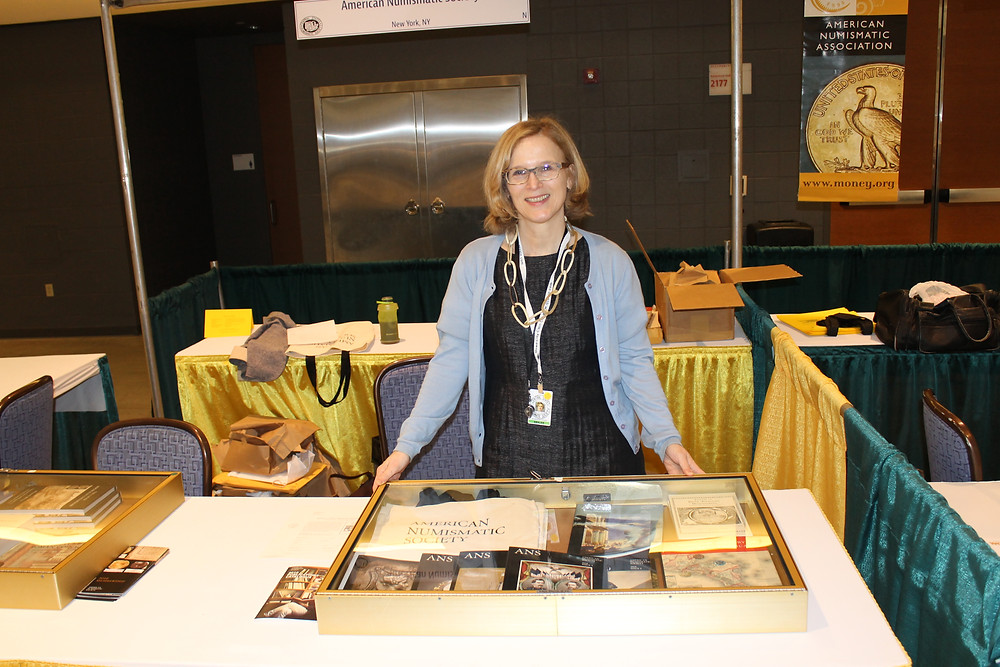 American Numismatic Association staff member sitting at the ANA table smiling.