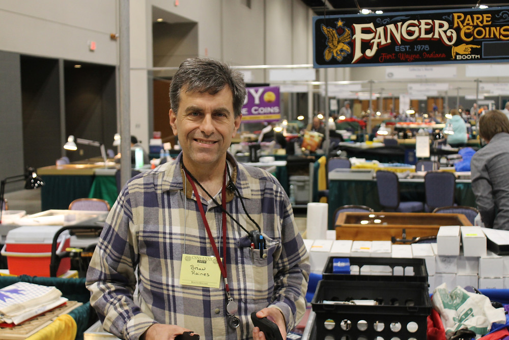 Coin dealer Brian Raines standing at his table on the bourse floor smiling.