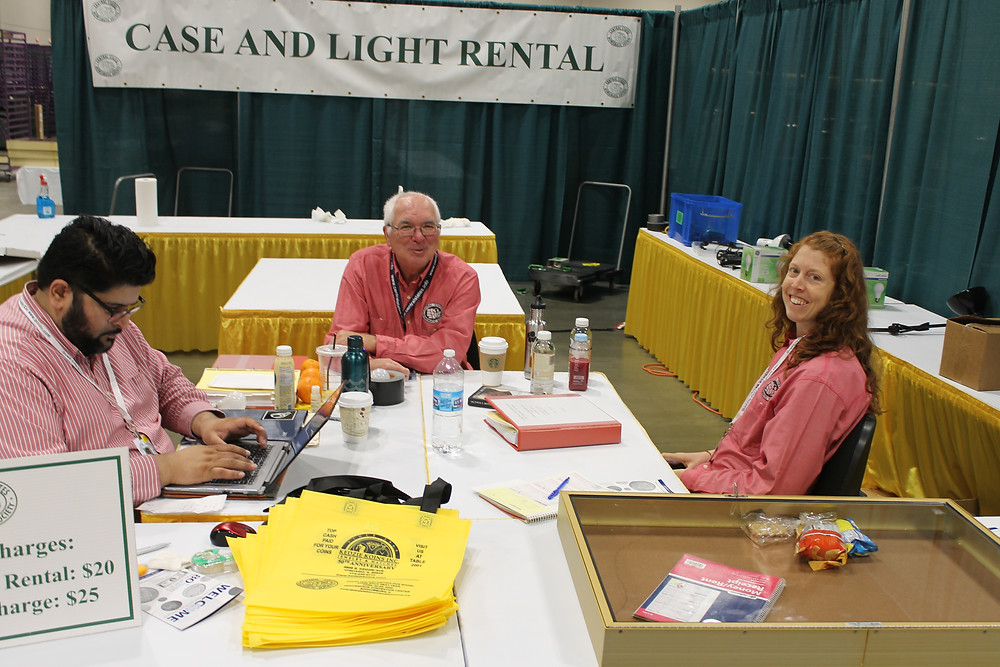 Three Central States staff members in pink shirts sitting in the Case and Light rental area.