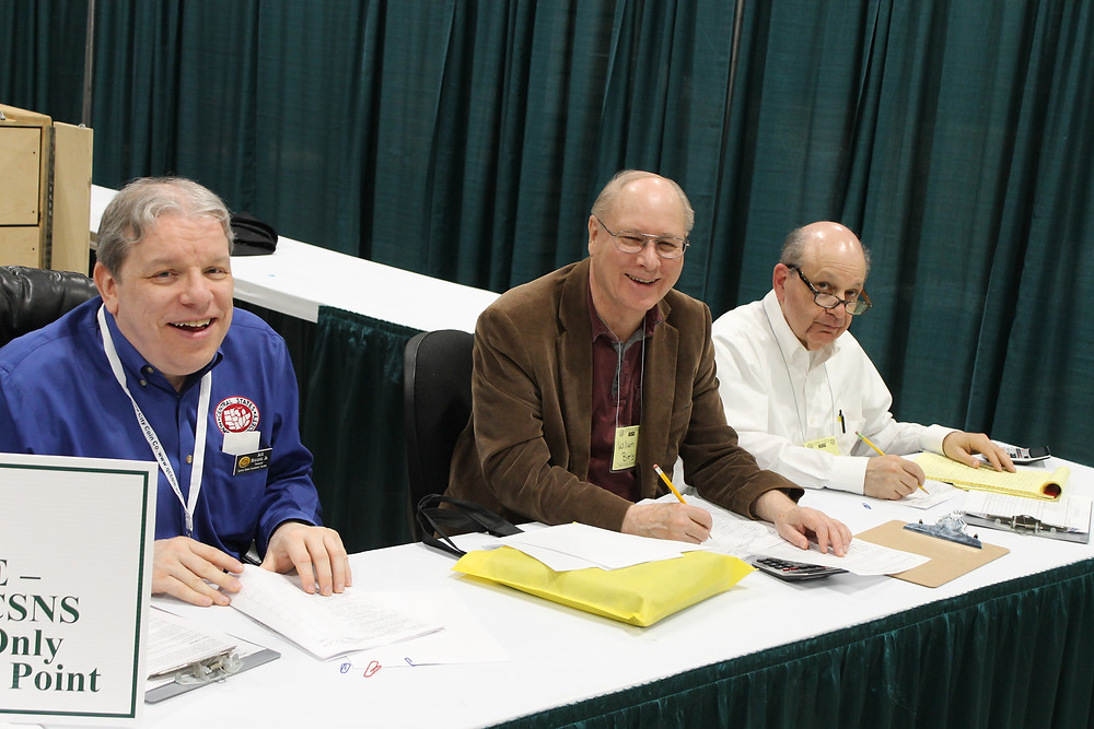 Central States exhibit judges comparing notes and tallying scores.