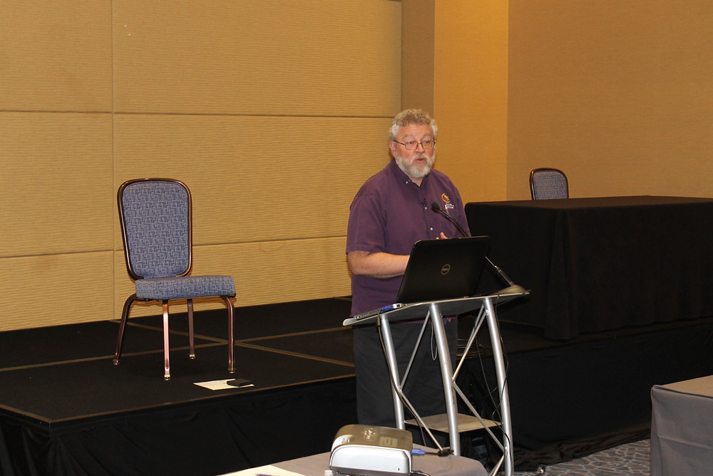 American Numismatic Association staff member Rod Gillis standing at a podium giving a program.
