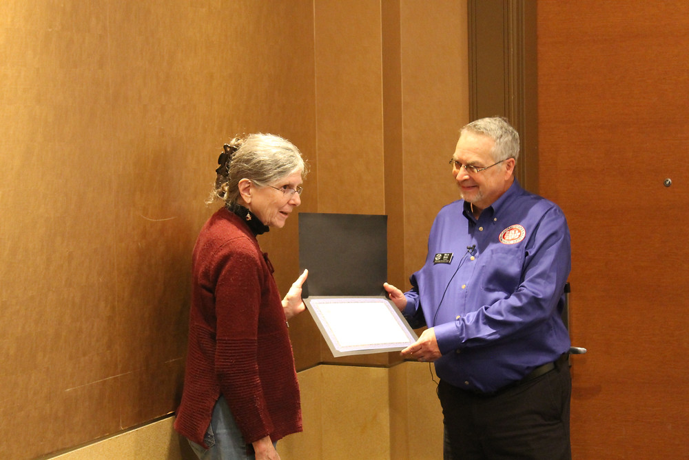 Central States President Mitch Ernst presented with a certificate for presenting a program at the Women In Numismatics meeting.