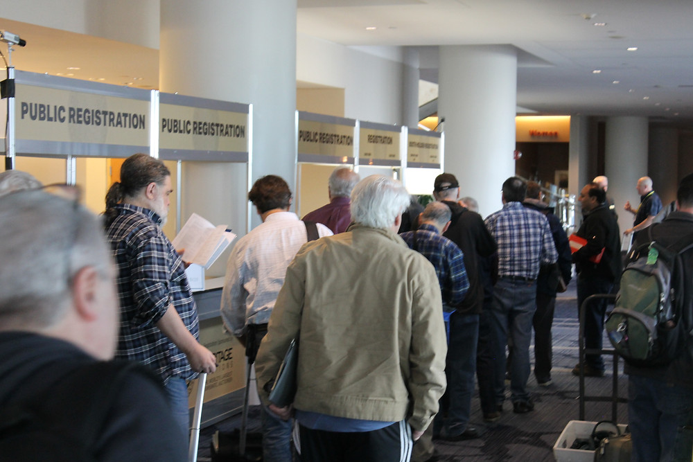 Long line of public attendees waiting in line at the registration desk for the 80th Anniversary Convention.