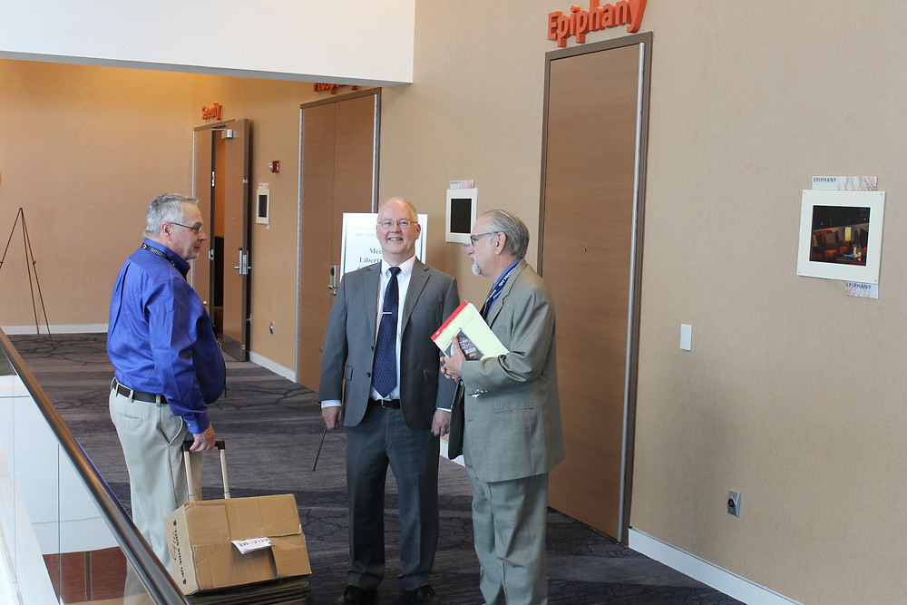Central States President talking in a hallway with Don Kagin and David Harper.