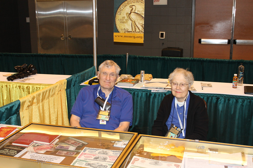 John and Nancy Wilson sitting at the American Numismatic Association table