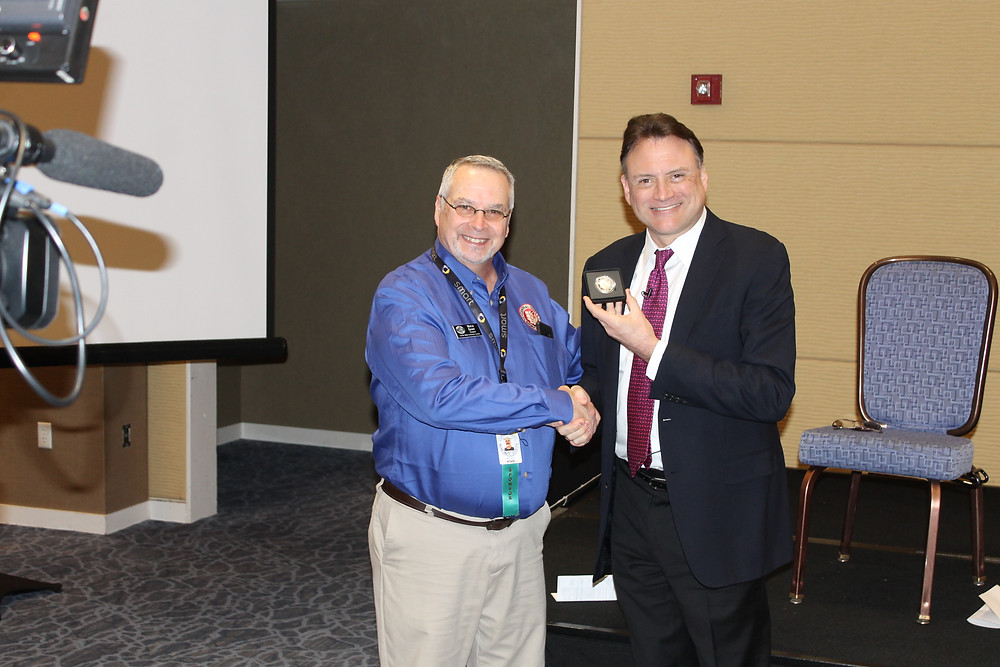 Central States President Mitch Ernst shaking hands with Heritage Auctions President Greg Rohan.