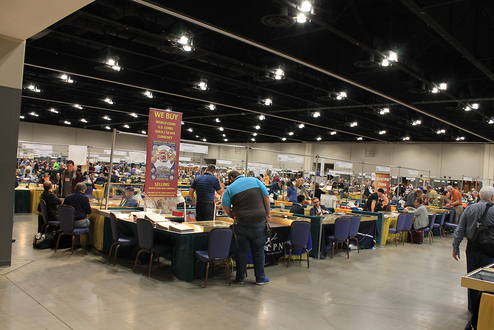 Image of the bourse floor at the Central States 80th Anniversary convention. Many dealers and public attendees walking around.