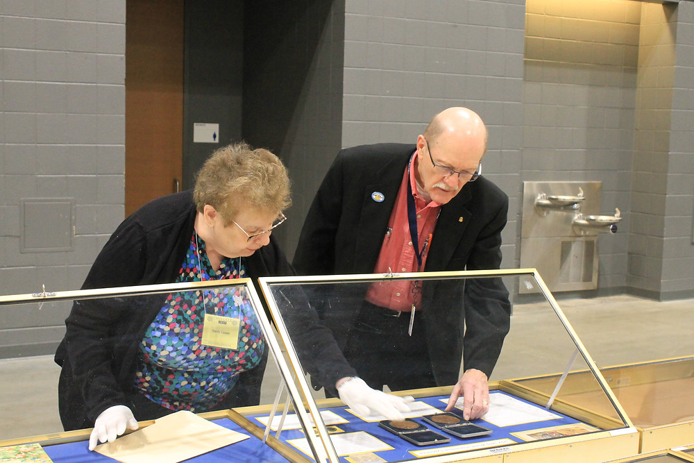 Two judges evaluating an educational exhibit display case.