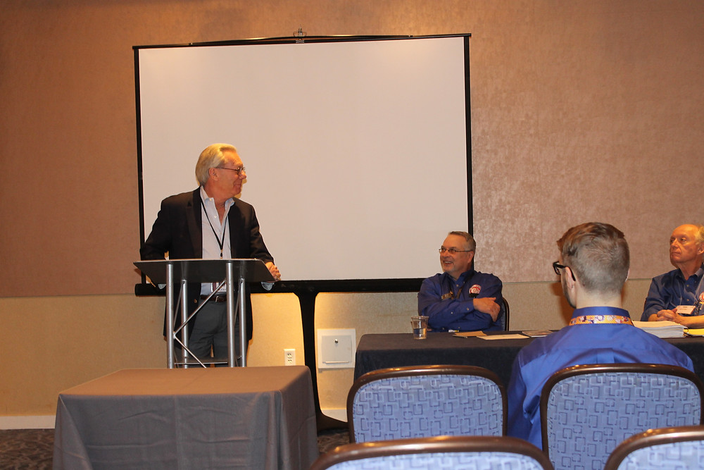 PCDA President standing at a podium announcing joining with Central States Numismatic Society. Central States President Mitch Ernst and Convention Chairman Kevin Foley are in the background.