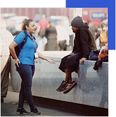 Woman with blue shirt speaking with man wearing all black who who is sitting on a ledge