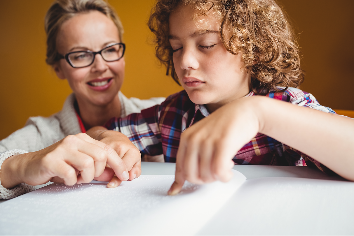 woman wearing glasses teaching young boy who is reading braille