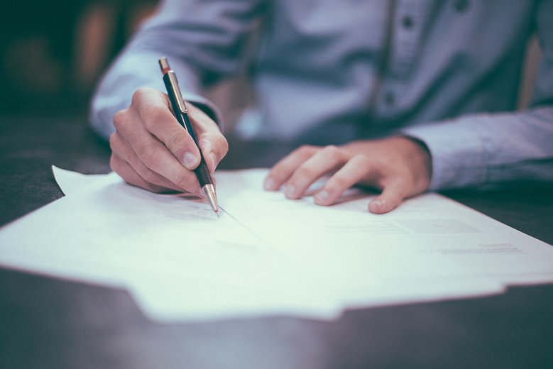 A person with pen signing documents