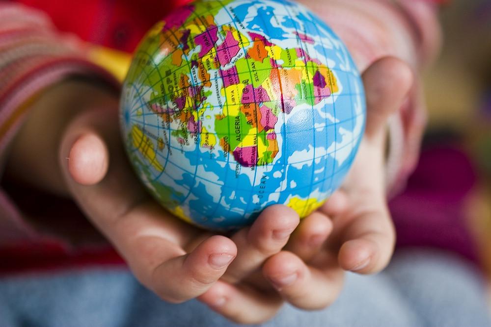Les mains d'un enfant tiennent Mère la terre avec Amour