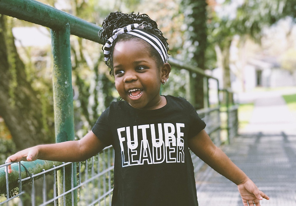 "Adorable African American girl about 4 years old. Girl sports a black t-shirt which reads ""Future Leader"" in white lettering and black-and-white ribbon in her hair."