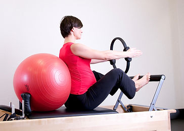 pregnant woman on pilates reformer bed with ball