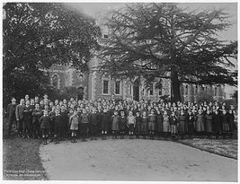 An old black and white photograph of children standing in front of a large building