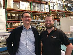 Two smiling men inside warehouse