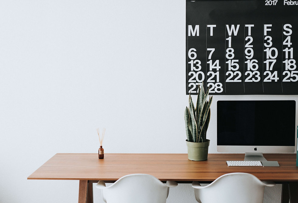 Home office with calendar, imac desktop, and plant