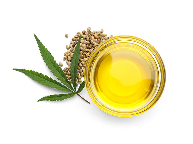 Bowl with hemp oil, leaf and seeds on white background, top view.jpg