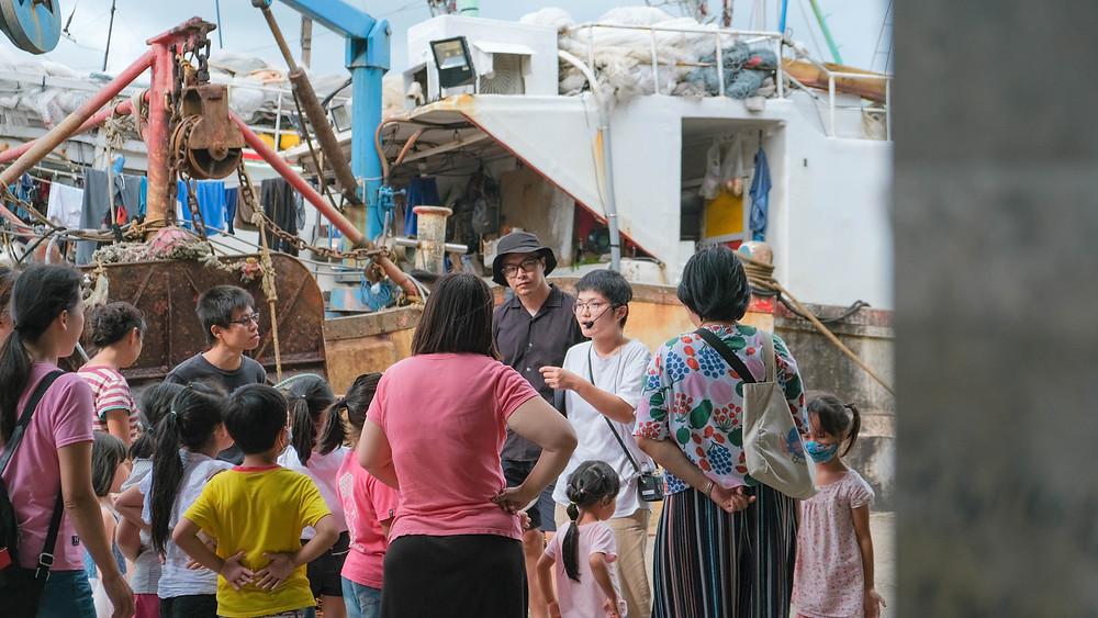 星濱山帶著大小朋友走出戶外實地觀察,每個人都很專注聆聽漁港故事。