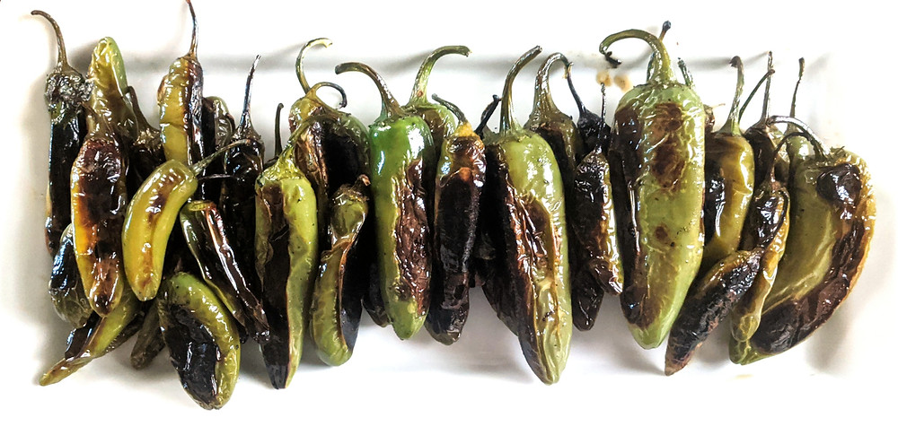 A neat row of charred peppers avoid direct eye contact with the camera and cameraman that they just assaulted during roasting. Tit for tat, I guess.