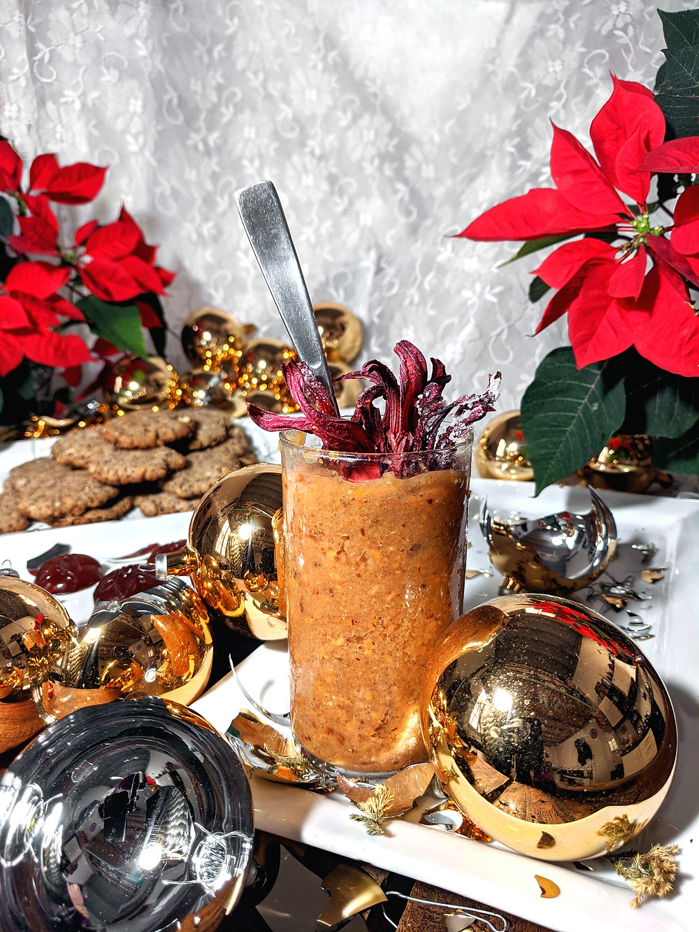 Ponche Granita, photographed by Tim @ Pinchido.  A glass of a reddish/beige slush sits among classic golden broken christmas ornaments with shards of glass covering the trays of cookies and ponche gummies.