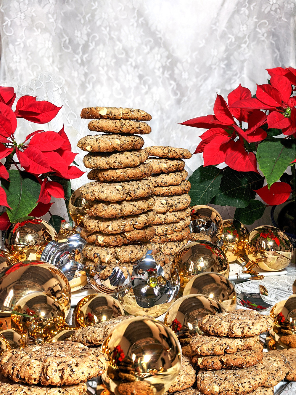 An unbelievable amount of cookies stacked in towers between red poinsettias and golden shards of fallen Christmas tree ornaments.
