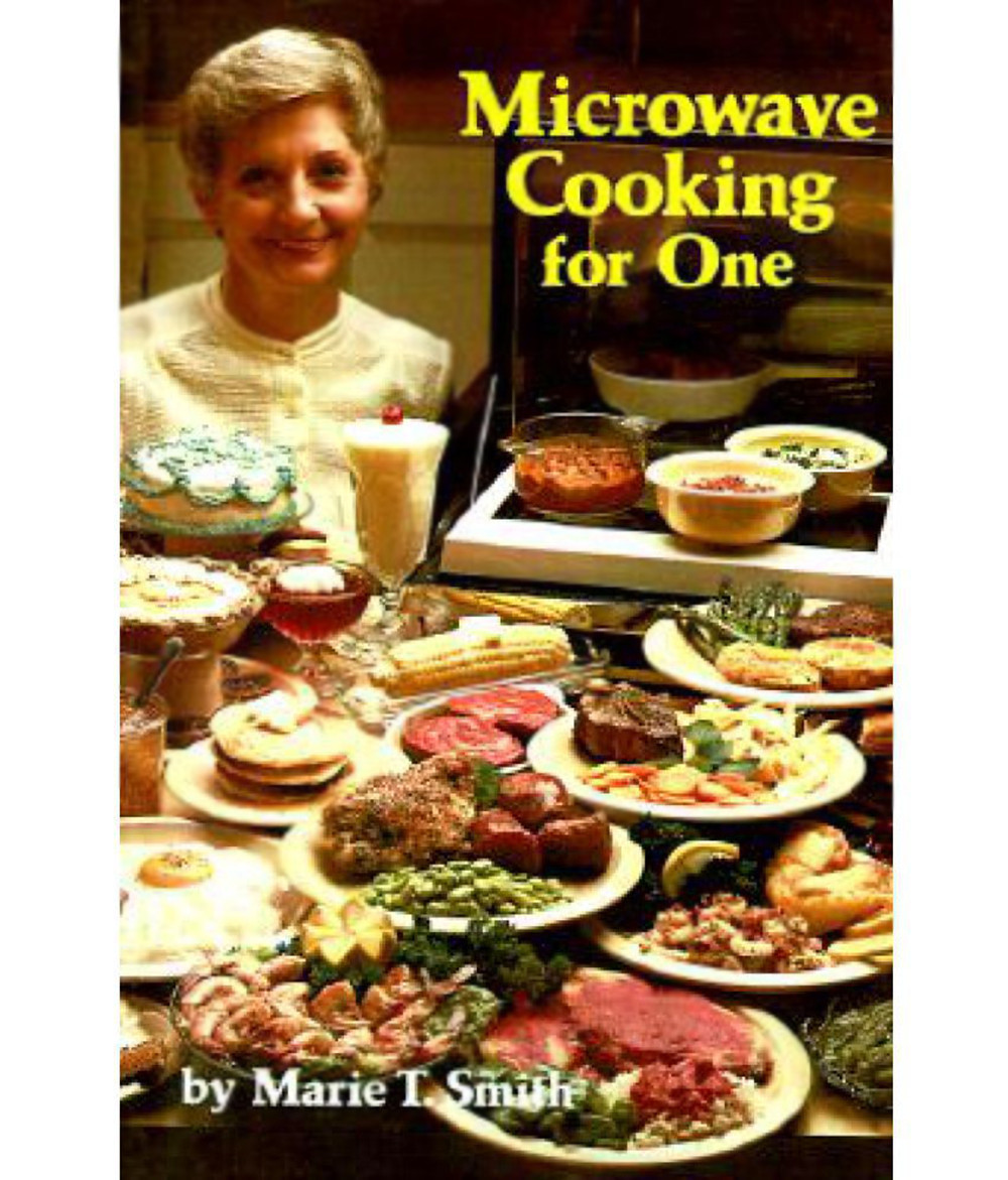 """The cover of the classic cookbook """"Microwave cooking for one,"""" with a forced-smile wearing prude showing off her self-meals to nobody because she's alone."""