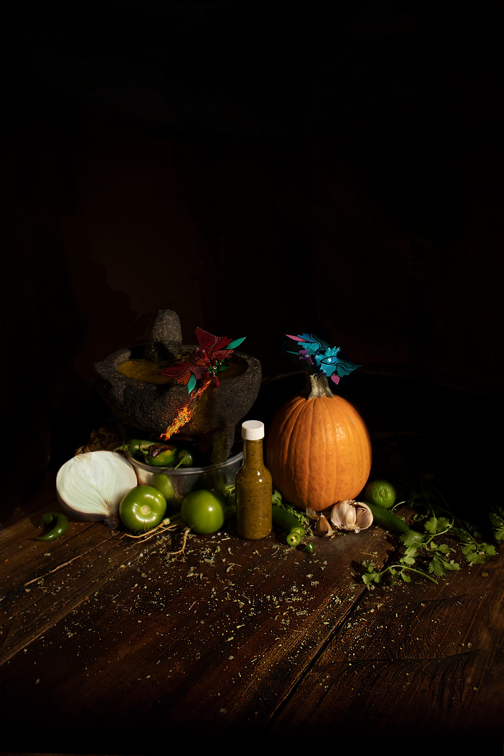 Tiny mythical Mexican creatures perched atop a pumpkin and molcajete, roasting the peppers for the salsa with their fire breath.