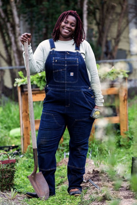 The most infectious smile you'll ever experience shines from the face of Tiffany Washington, founder and farmer of Dobbin-Kauv Garden in Austin, TX. She stops her hard work to pose with her shovel and overalls that should be dirty but the sponsor Carhartt surely thought that clothes that look like they've been actually used are a bad visual mechanic. Get a grip, Carhartt.  Farmers get dirty. We know they're from you because this is on your website. You made Tiffany stop what she was doing to stay clean. Super rude...