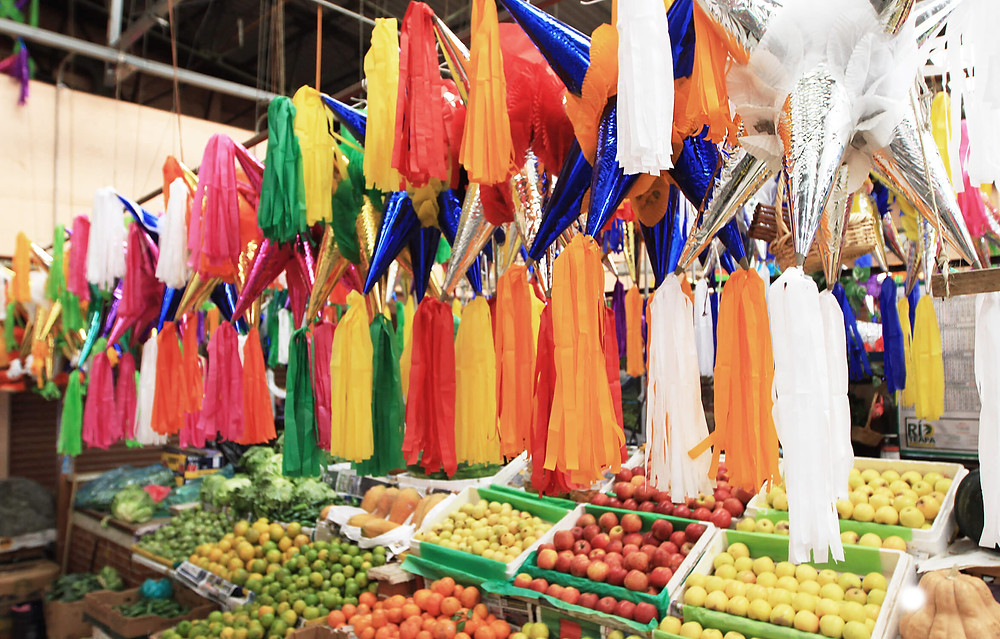 A traditional market in Mexico shows rows of piñatas hovering over neatly stacked apples from Washington State, an absurd item to import into a country with every landscape and climate imaginable, save for the tundra.