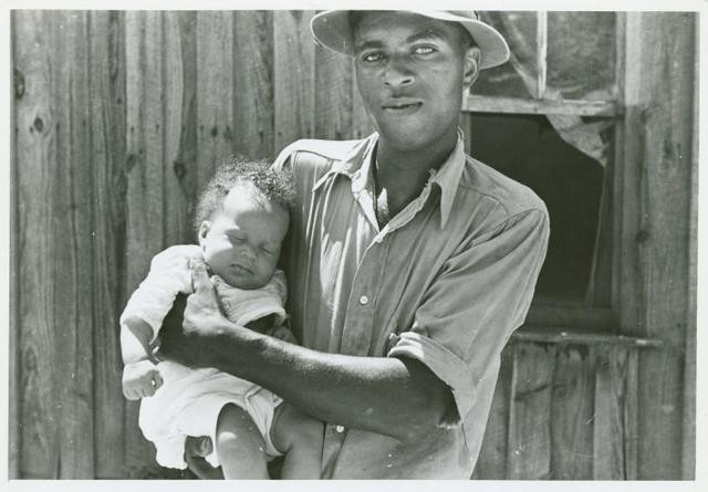 An unbelievable gorgeous man holding a sleeping baby which I'm pretending isn't his because it ruins the plans I have for us if we ever figure out this time-travel thing. Part of a collection of photographs depicting black tenant farmers in America. Whew it's getting hot in here. Are you hot? I'm hot. I'm ... I'm gonna get some water. Take a cold shower maybe... Negro tenant farmer, Lee County, Mississippi. Rothstein, Arthur, 1915-1985, photographer United States. Resettlement Administration.