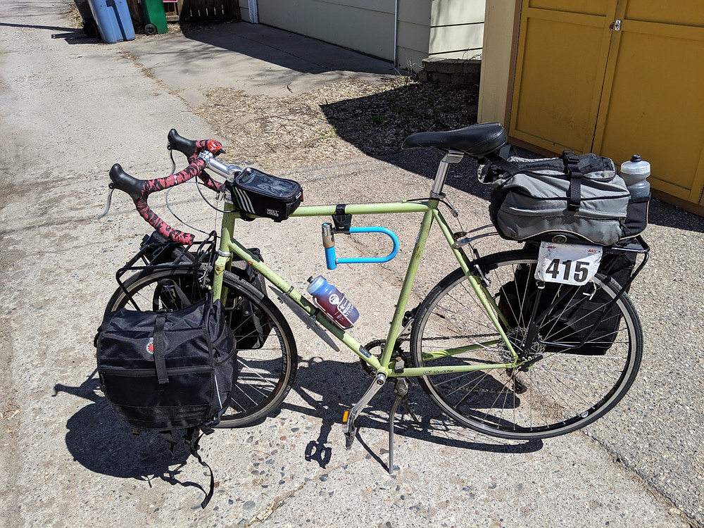 My green Surly Crosscheck bike with two panniers on the front, a rack trunk and one pannier on the back, and a top tube bag