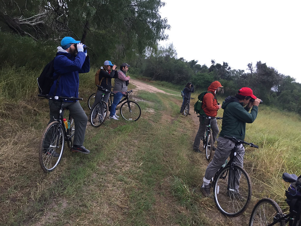 People with bikes looking through binoculars