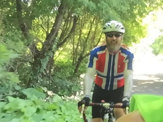A picture of me biking in my Norwegian flag jersey on the MS tRAM trip in 2018
