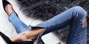 Close up di slim donna gambe in jeans e scarpe da ginnastica
