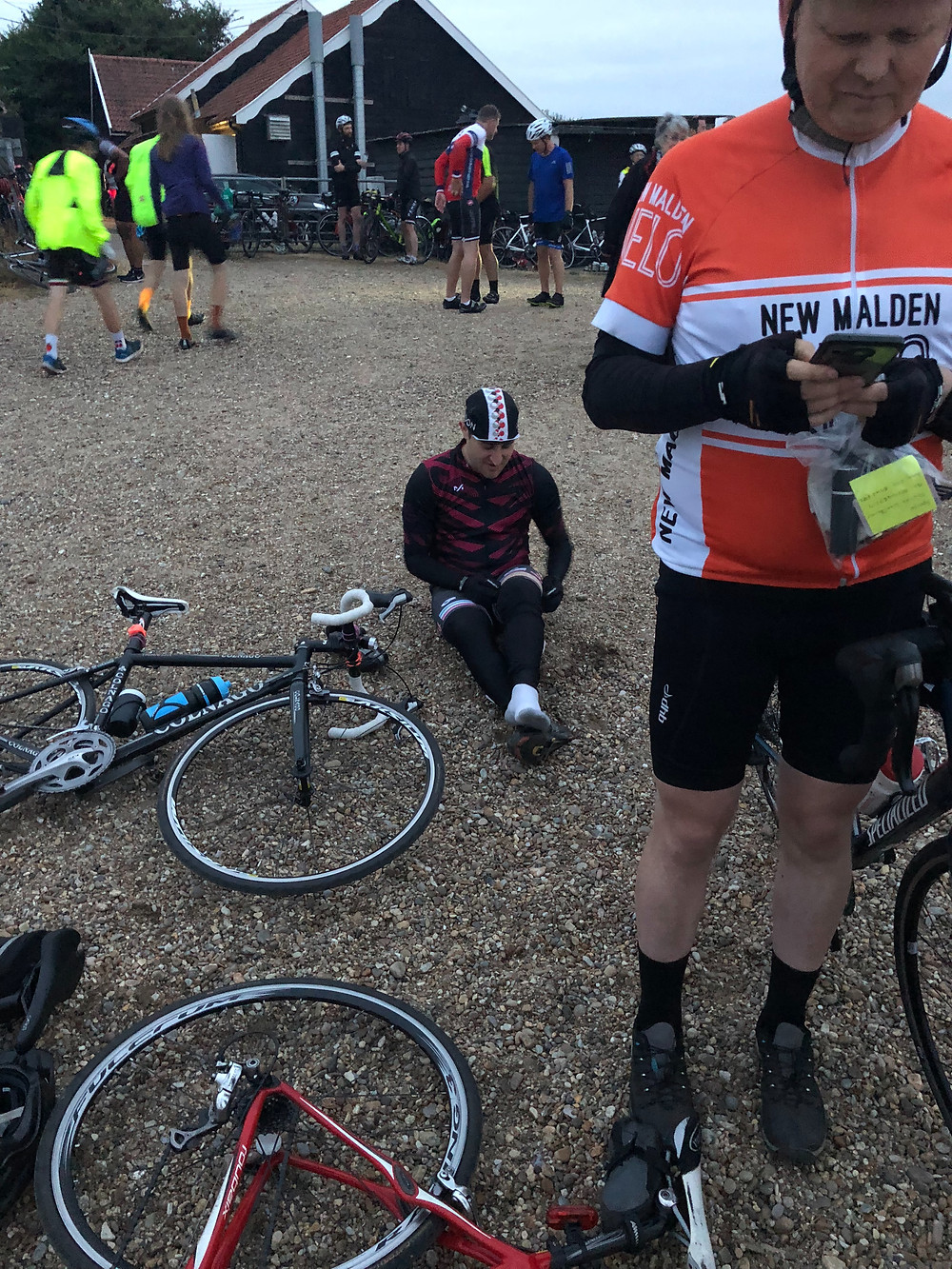 New Malden Velo Cycle club sitting on the beach at Dunwich