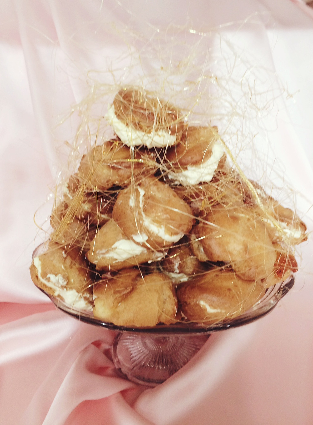 Choux buns on a cake stand covered in spun sugar