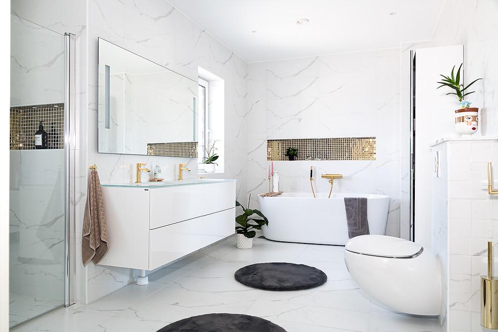 Ett badrum i marmor med badkar, toalett, dubbla handfat och en duschkabin. Kranar och dusch i guld.