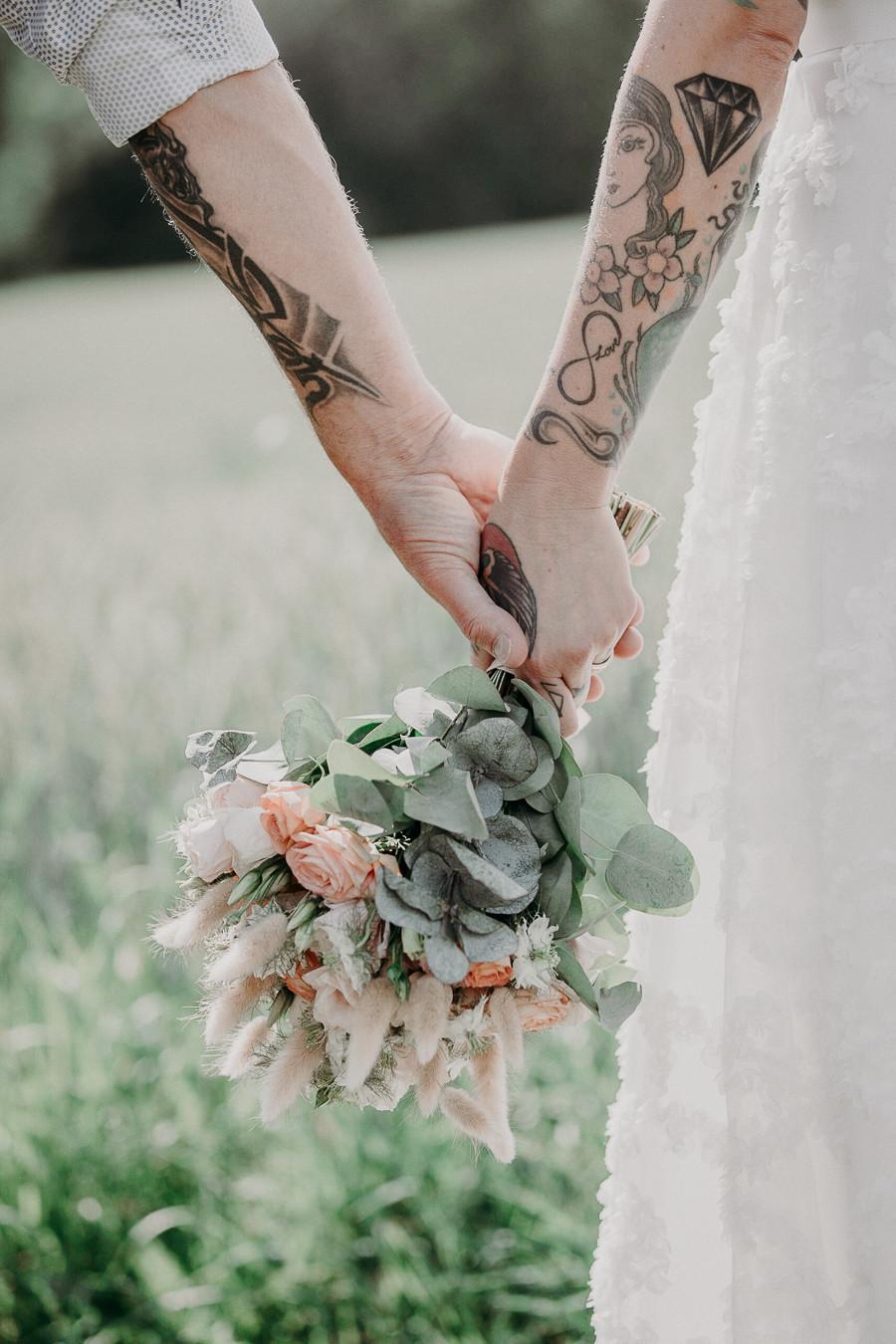 Bilden visar händerna på ett brudpar som håller i en bröllopsbukett