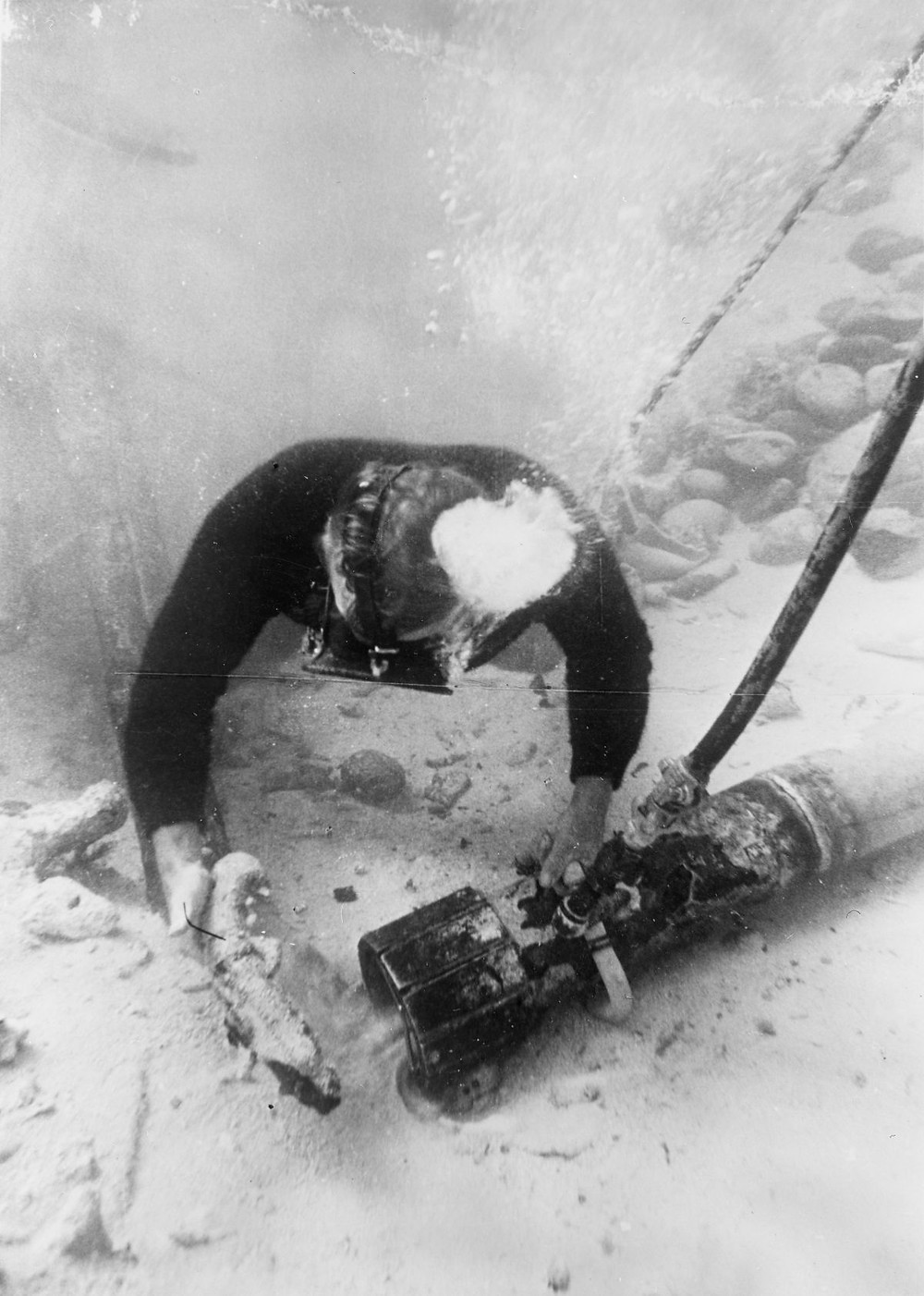 "Treasure diver Art McKee recovering a coral encrusted flintlock pistol from the ""El Capitana"" wreck using surface supplied air - Florida Keys, Florida, 1955."