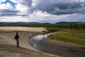 A horseshoe bend formed by the Kobuk River separating the Arctic sand dunes and the tundra landscape.