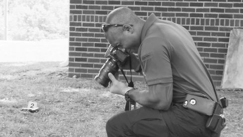 Forensic Investigator Taking picture of evidence