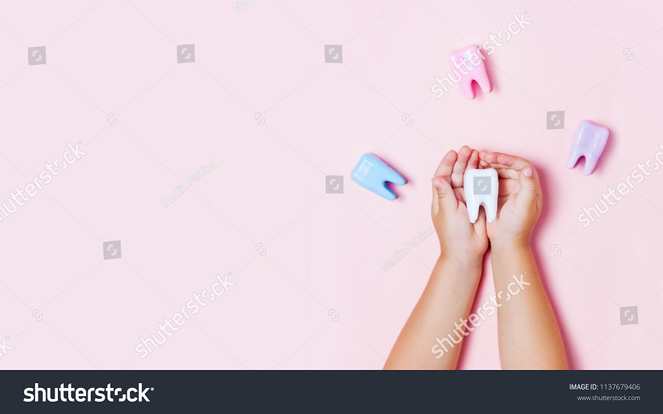 stock-photo-child-s-hands-holding-big-tooth-and-toothbrush-on-pink-backgroubd-healty-care-
