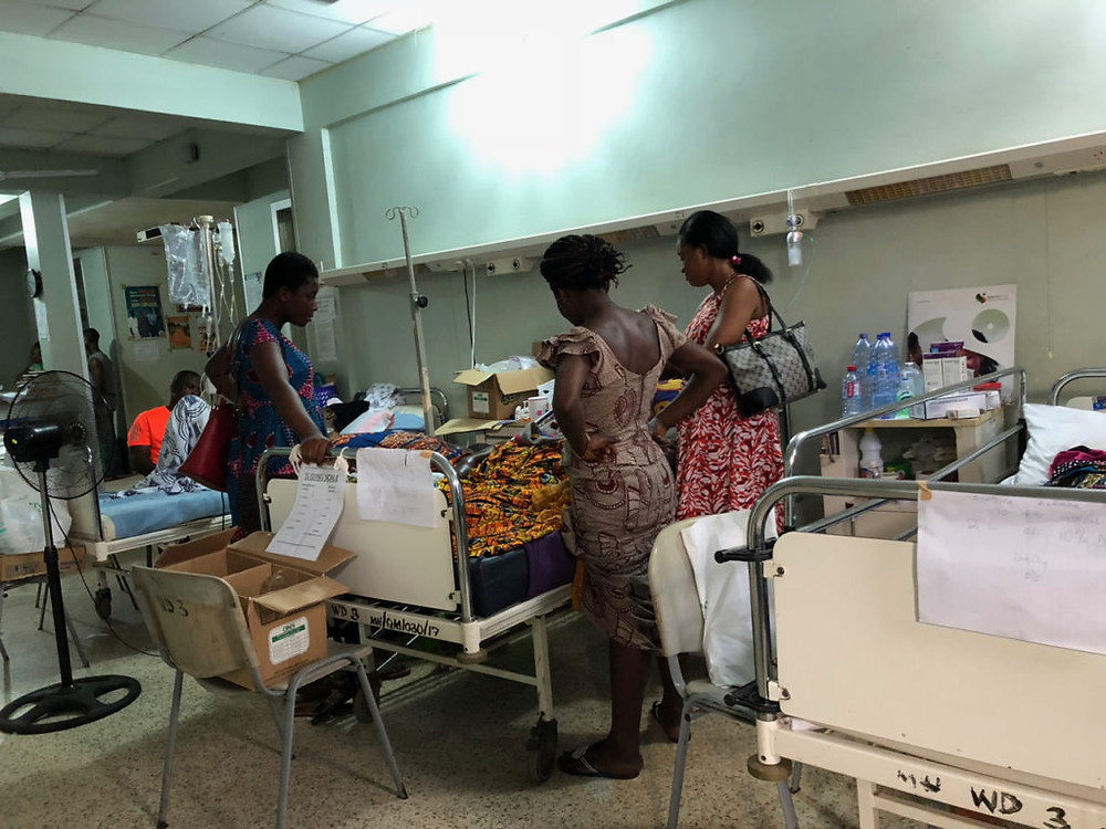 Family members at a patient bedside on the ward (medicine in a West African country)